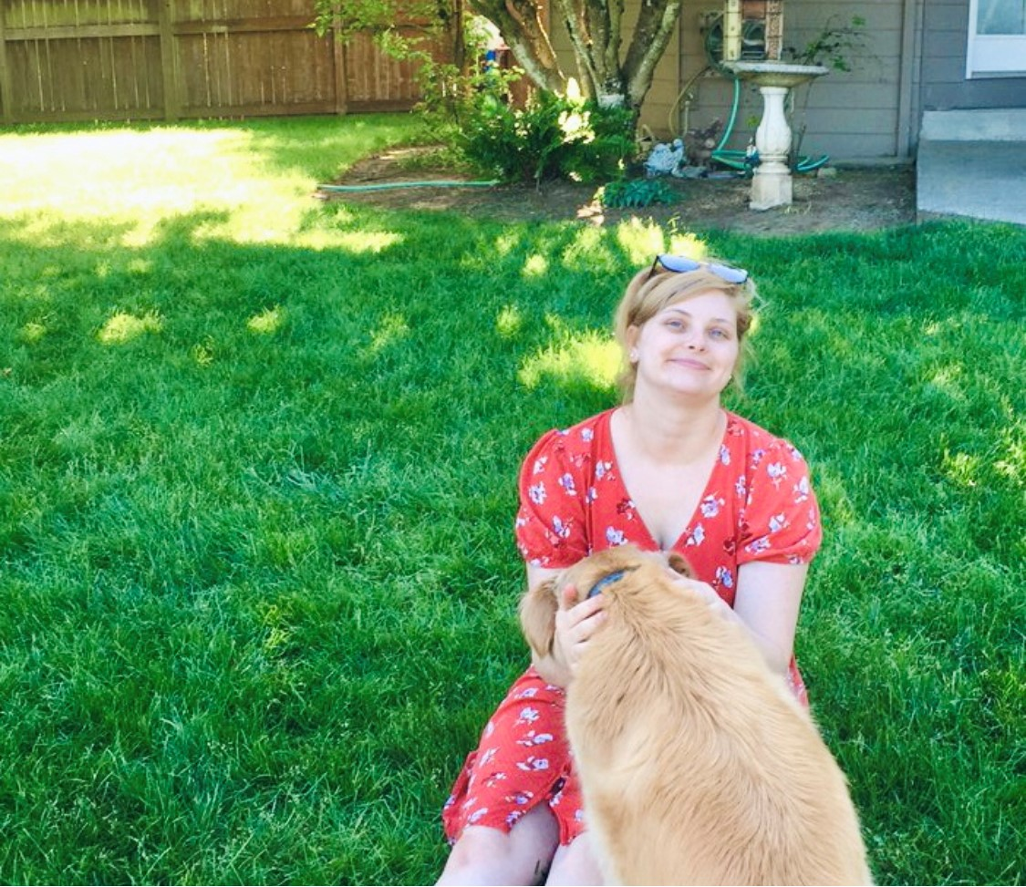 Steph sitting outside with her sister's golden retriever in her lap.